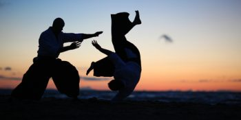two silhouetted people training aikido with a beautiful background