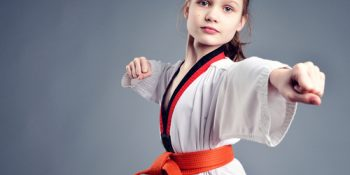 a little girl practising aikido dressed in her martial arts robe